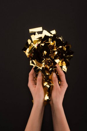 partial view of female hands with golden confetti isolated on black