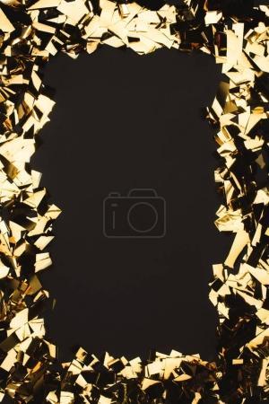 Photo pour Vue rapprochée de confettis dorés étincelants isolés sur noir - image libre de droit