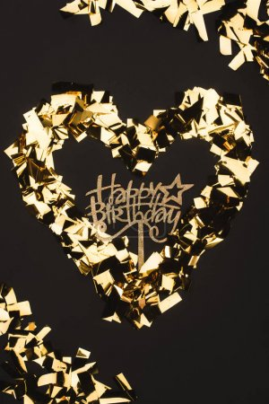 top view of happy birthday sign and golden confetti isolated on black
