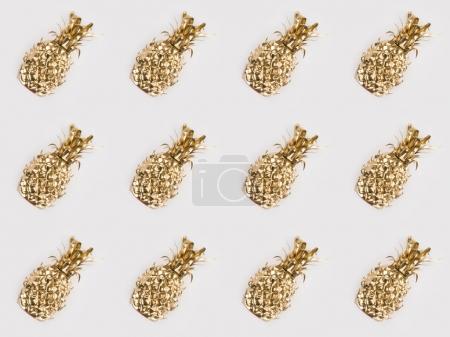 full frame of arranged golden pineapples isolated on grey