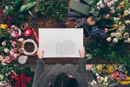 Foto de Imagen recortada de Floreria con hoja vacía del papel en las manos por encima de la mesa de trabajo - Imagen libre de derechos