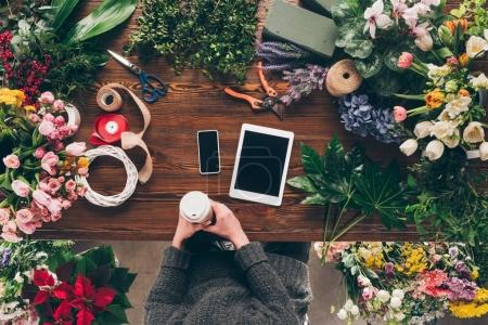 Photo for Cropped image of florist holding coffee in paper cup above working place - Royalty Free Image