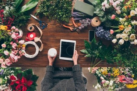 cropped image of florist holding coffee in paper cup and tablet in hands