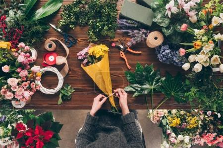 cropped image of florist tying ribbon on bouquet at flower shop