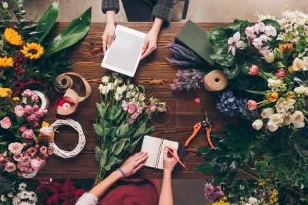 Photo for Cropped image of florists with tablet and notebook at work - Royalty Free Image