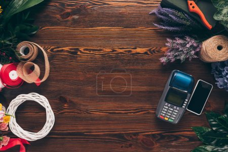 top view of terminal for payment and smartphone on table in flower shop