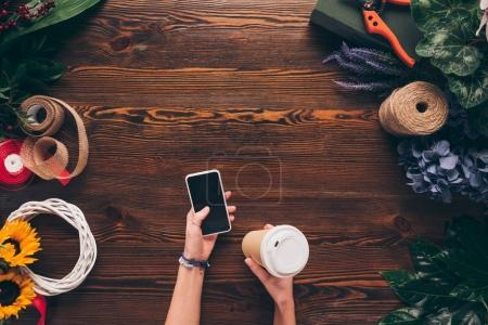 Photo for Cropped image of florist holding disposable coffee cup and smartphone in hands - Royalty Free Image