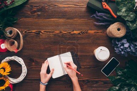 Photo pour Image recadrée de femme fleuriste écrire quelque chose au travail pour ordinateur portable - image libre de droit