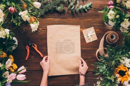 cropped image of florist holding empty sheet of paper in hands