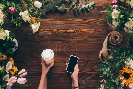 cropped image of florist holding coffee in paper cup and smartphone in hands