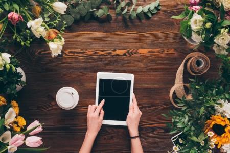 cropped image of florist using tablet at work