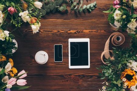 Photo pour Vue de dessus du café dans la tasse de papier, smartphone et tablette sur table avec des fleurs - image libre de droit