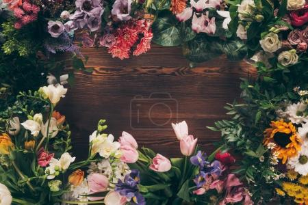 top view of frame of colored flowers on wooden table