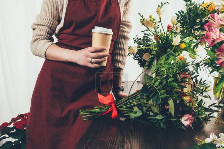 cropped image of florist holding coffee in paper cup and leaning on working table