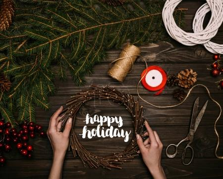 Photo for Top view of florist hands holding Christmas wreath with Happy holiday lettering on wooden tabletop - Royalty Free Image