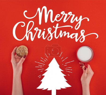 Photo for Cropped view of female hands with homemade oatmeal cookie and cup of milk, isolated on red with Merry christmas lettering and christmas tree - Royalty Free Image