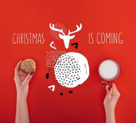 Photo pour Vue recadrée de mains féminines avec biscuits de farine d'avoine fait maison et tasse de lait, isolé sur le rouge avec Noël sont venir lettrage - image libre de droit