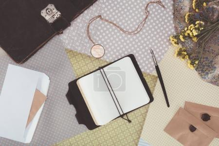 top view of opened notebook with envelopes over pack paper background