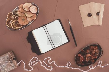 top view of notebook, jewelry box, dried fruits and envelopes over brown paper background