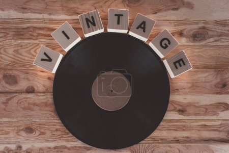 top view of cubes with letters and vinyl record over wooden background