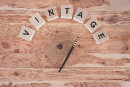 top view of cubes with letters, envelope with seal and fountain pen over wooden background