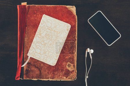 Photo for Top view of bible with smartphone and earphones on wooden table - Royalty Free Image