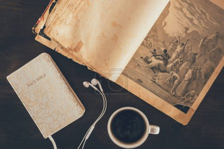 Photo for Top view of holy bible, earphones and cup on table - Royalty Free Image