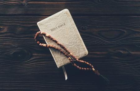 top view of closed holy bible and rosary with cross on wooden table