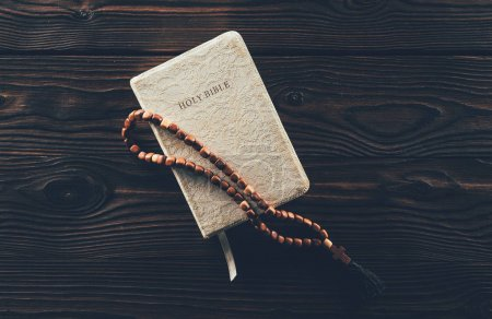 Photo for Top view of closed holy bible and rosary with cross on wooden table - Royalty Free Image