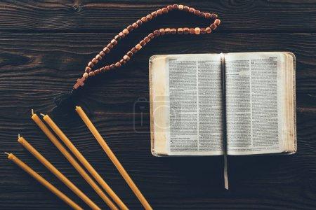 Foto de Vista superior de Biblia abierta con Rosario y velas en la mesa - Imagen libre de derechos