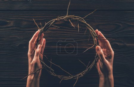 cropped image of woman holding crown of thorns in hands
