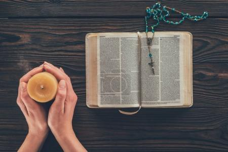 Photo for Cropped image of woman holding candle above wooden table with bible - Royalty Free Image