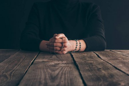Photo for Cropped image of nun sitting at table with rosary and praying - Royalty Free Image