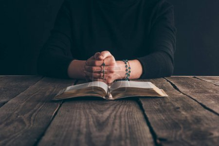 cropped image of woman sitting at table with rosary and bible and praying
