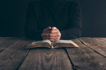 Photo for Cropped image of nun sitting at table with bible and praying - Royalty Free Image