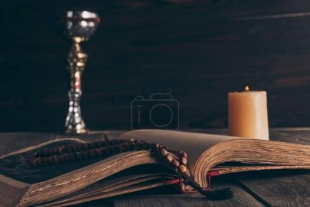 Open holy bible with rosary, chalice and candle on...
