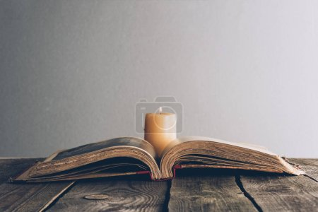 Photo for Open holy bible with candle on wooden table - Royalty Free Image