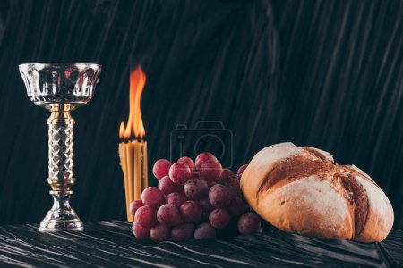 Photo for Bread with grapes, chalice and candles on black fabric, Holy Communion - Royalty Free Image