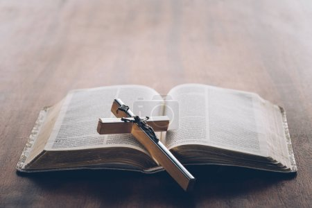 christian cross on open holy bible