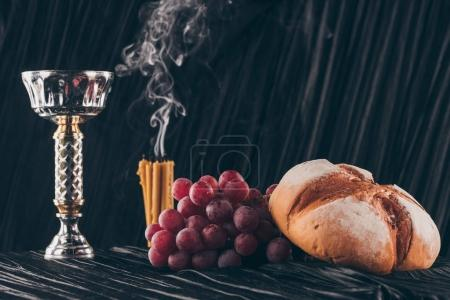 Photo for Bread, grapes, candles and chalice on dark fabric for Holy Communion - Royalty Free Image