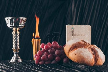 holy bible, surface and christian cross with candles on dark table for Holy Communion