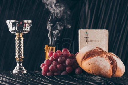 Photo for Food, bible, chalice and christian cross on dark table for Holy Communion - Royalty Free Image