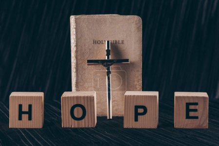 wooden cubes with word Hope and bible with cross on black table