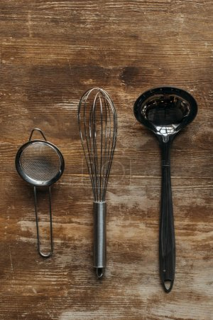 top view of metallic kitchen utensils on wooden table