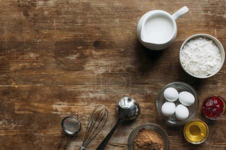 top view of fresh ingredients for pastry and utensils on wooden table