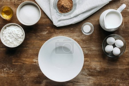 top view of ingredients for pastry and empty bowl on wooden table