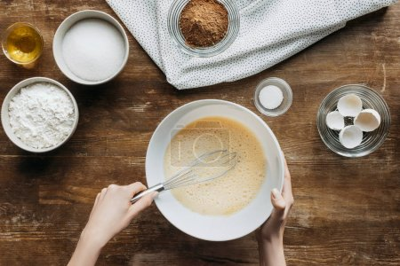 cropped shot of woman whisking liquid for baking pancakes on wooden table