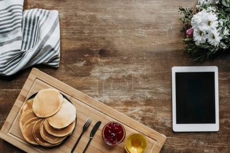top view of breakfast with pancakes and digital tablet on wooden table
