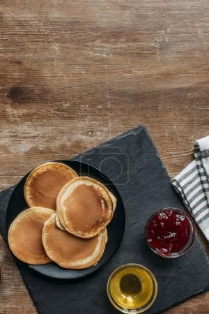 top view of delicious pancakes with maple syrup and jam on wooden table