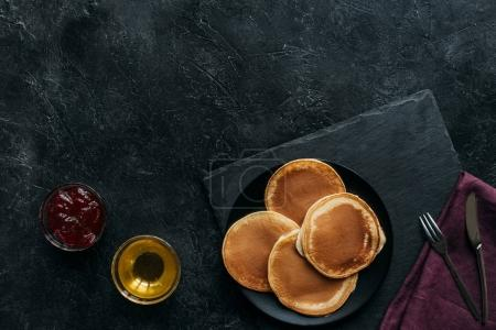 top view of pancakes with jam and maple syrup on black concrete surface